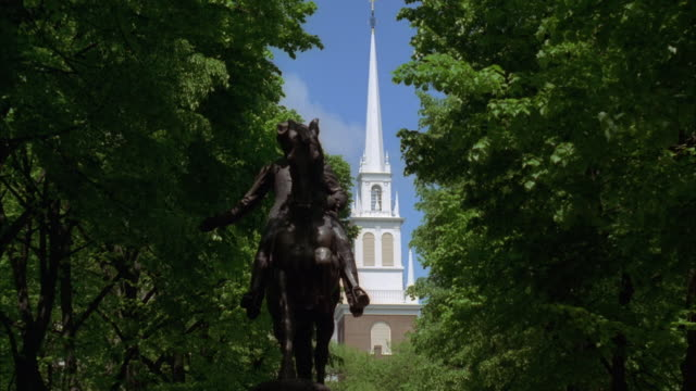 wide angle looking up at statue of paul revere on his horse. white steeple of old north church in right bg. paul revere mall in north end of boston. trees in bg. - old north church stock videos & royalty-free footage