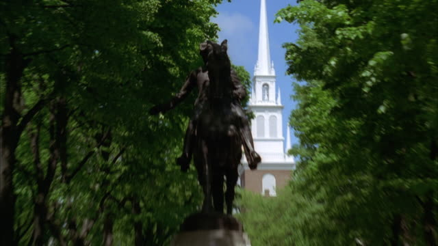 zoom in to statue of paul revere on his horse in paul revere mall. steeple of old north church in bg. trees line street. tourists visible. - old north church stock videos & royalty-free footage