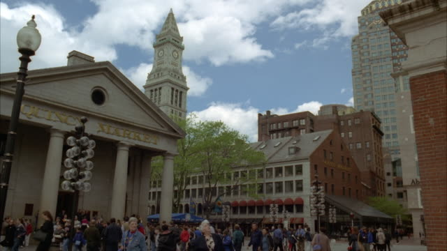 vídeos y material grabado en eventos de stock de wide angle of quincy market in dock square, boston. pedestrians walking around in square. customs house clock tower in bg. - massachusetts