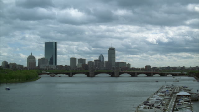 wide angle of charles river with longfellow bridge in bg. boats and docks on right side of screen. downtown boston skyline. cloudy sky. ferry boat. marina in fg. - longfellow bridge stock videos and b-roll footage