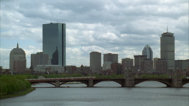 wide angle of charles river with longfellow bridge in bg. downtown boston skyline. cloudy sky. train traveling on bridge from right to left. - longfellow bridge stock videos and b-roll footage