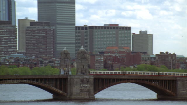 pan right to left as train moves across longfellow bridge. boston skyline visible. high rises, skyscrapers, and office buildings. boats visible in boston harbor. - longfellow bridge stock videos and b-roll footage