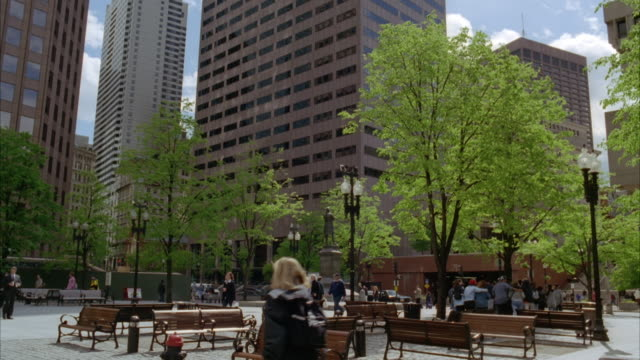 wide angle of courtyard or park area in downtown boston. people sit on benches while others walk around. high rises, skyscrapers, and office buildings. - courtyard stock videos & royalty-free footage