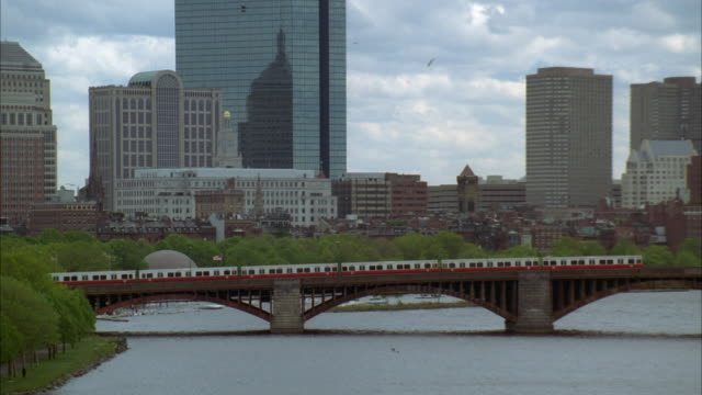 pull back from train traveling left to right on longfellow bridge to wide angle of charles river with downtown boston skyline. high rises, skyscrapers, and office buildings. cloudy. - longfellow bridge stock videos and b-roll footage
