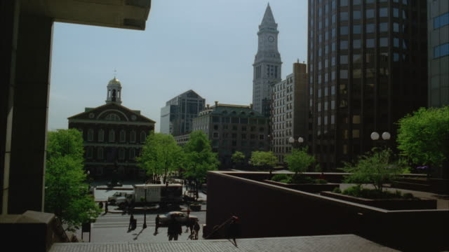 wide angle looking at faneuil hall located in center of downtown boston. high rise office buildings and custom house clock tower in bg. pedestrians walking on sidewalks and up and down stairs. - custom house tower stock videos & royalty-free footage
