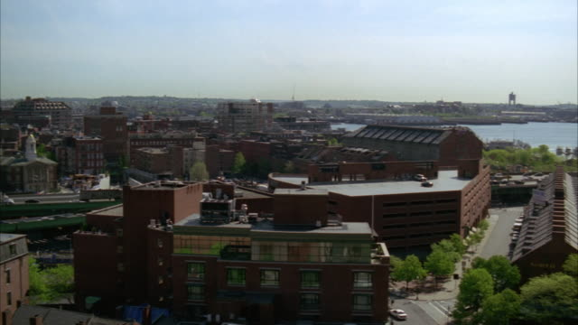 pan left to right along freeways and streets to high rise office buildings and custom house clock tower in downtown boston. cities. boston harbor and charles river visible. crane in fg. - custom house tower stock videos & royalty-free footage
