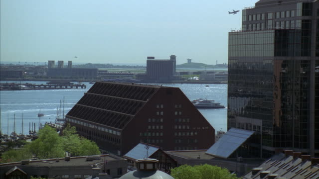 wide angle of triangular shaped building on bank of charles river in boston. industrial area in bg. cities. downtown. boats visible anchored in marina. small airplane flies by over harbor. - river charles stock videos & royalty-free footage
