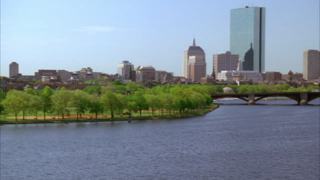 pan left to right along boston city skyline. longfellow bridge over charles river and boston harbor. high rises, skyscrapers, and office buildings. trees in park in fg. - longfellow bridge stock videos and b-roll footage