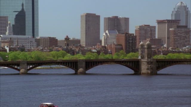 pan right to left along longfellow bridge with boston skyline in bg. red ferry in water. - longfellow bridge stock videos and b-roll footage