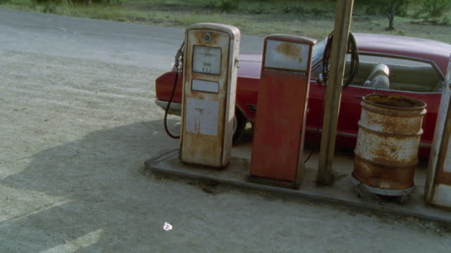 vídeos de stock, filmes e b-roll de medium angle of looking off porch of old gas station. old, rusty gas pumps in bg. red car stopped at pumps. dirt surface. - 1990