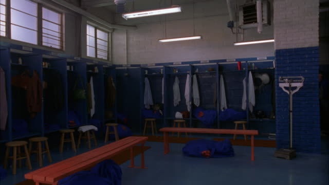 wide angle  inside locker room / see lockers and benches / scale in bg / locker room is blue - locker room stock videos and b-roll footage