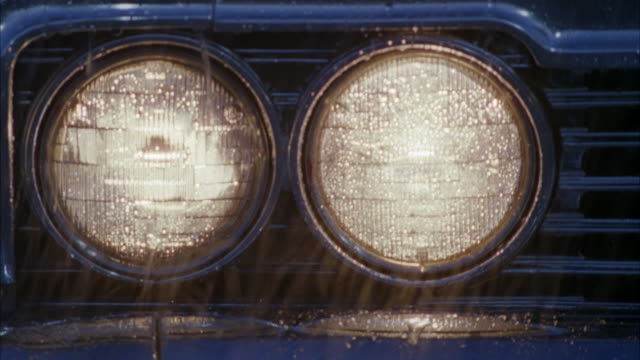 cam pans l-r to close up of headlights of a car / lots of rain in shot / headlights are on / end of shot cam pans up across hood of car - autoscheinwerfer stock-videos und b-roll-filmmaterial