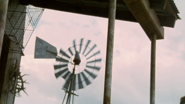 wooden support poles in fg holding up roof. old windmill spinning in bg. overcast skies - anno 2001 video stock e b–roll