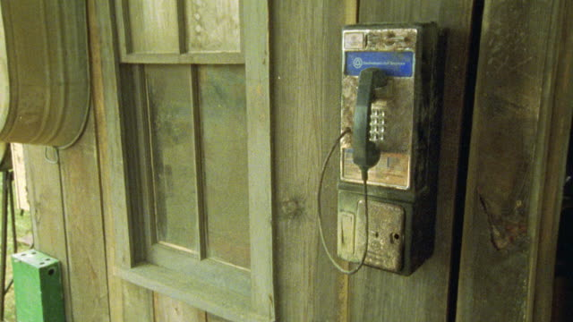 pay phone on outside wall of shack. telephones. - pay phone stock videos and b-roll footage