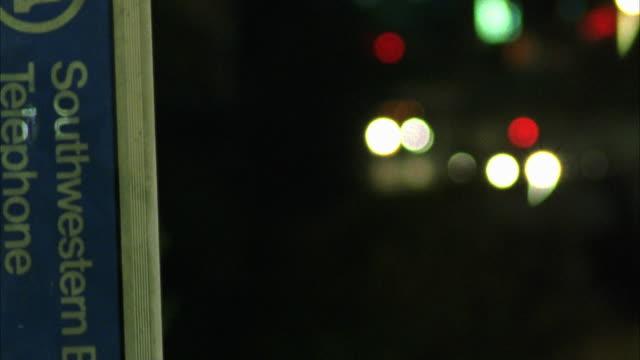 side view of pay phone booth. cars driving in right bg. matching shot to 2120-002 - telefonkiosk bildbanksvideor och videomaterial från bakom kulisserna