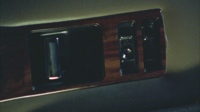 EST. CLOSE ANGLE INSERT OF INTERIOR CAR DOOR PANEL. LOCK MECHANISM UNLOCKS AND LOCKS BY ITSELF TWICE. FINGER THEN MANUALLY LOCKS AND UNLOCKS IT. LOCK AND HANDLE IN WOOD FIXTURE.