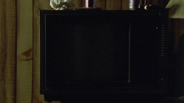 CLOSE ANGLE INSERT OF TELEVISION MONITOR. SCREEN SHOWS PLAYBACK OF COLOR BARS THEN  QVC OR HOME SHOPPING NETWORK PROGRAMMING.