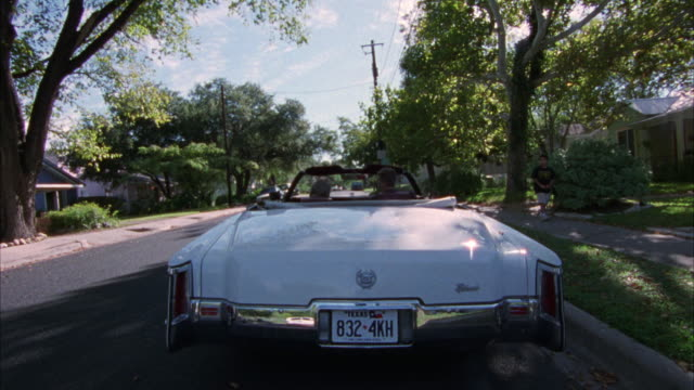 medium angle. back of white classic cadillac convertible in fg. two passengers. parked on right side of road in residential area. then drives forward away from camera. - convertible stock videos & royalty-free footage