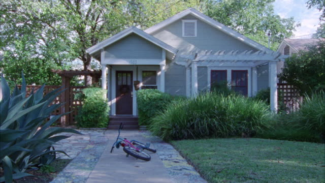 medium angle. small house in bg. grass yard with concrete walkway leading up to house in fg. house is gray with white trim. front yards. middle class. - middle class stock videos & royalty-free footage