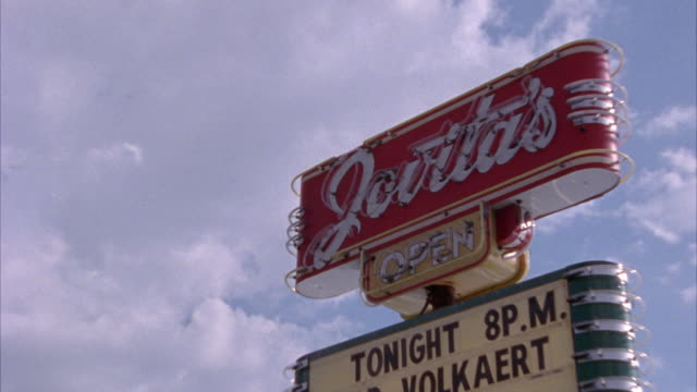 """est zoom in. looking up at neon sign that reads 'jovitas"""". red sign with white writing. sign on top of building. this sign is for jovita's mexican restaurant in austin. bars. could be used for nightclub. sign adverstising performance by """"redd volkaert ban - austin texas stock videos & royalty-free footage"""