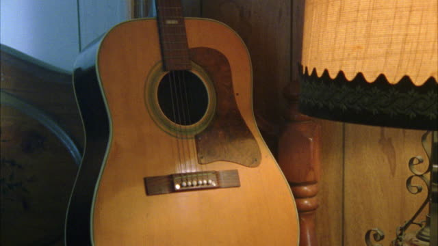 est. pan up close-up of brown acoustic guitar standing upright on a chair. pans down to night stand with lamp, red candle, telephone and an empty bottle of beer on it. - ギター点の映像素材/bロール