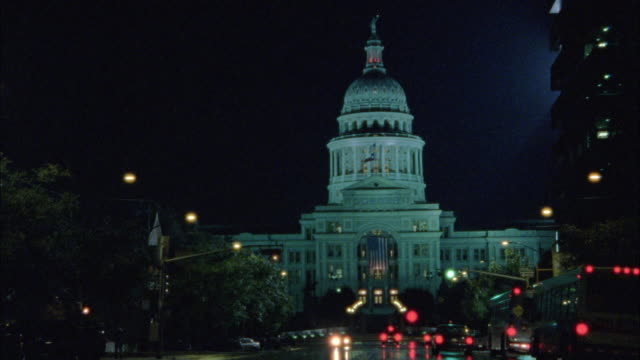 wide angle. texas state capitol located in austin.  building lit up in bg. - texas state capitol building stock videos & royalty-free footage
