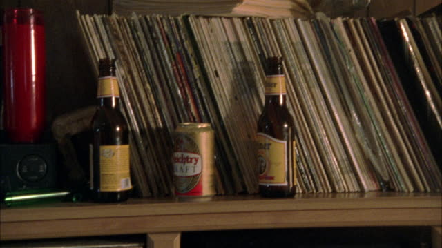 stockvideo's en b-roll-footage met empty beer bottles and records on shelf. pans r-l and down along shelf to small television set. then pans l-r up shelf to wall of pictures. - shelf
