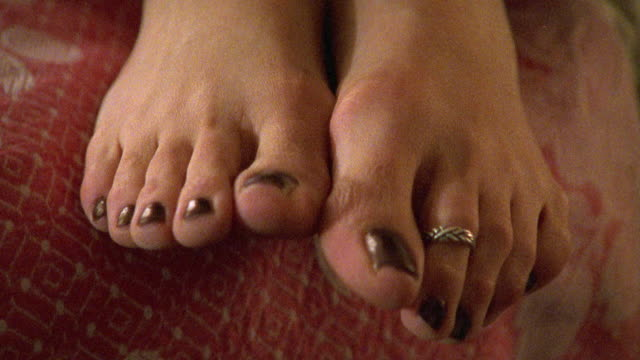 close angle. woman's feet wiggling on edge of bed. toe nails painted dark red with toe ring on her left foot. women rubs feet together. - foot stock videos & royalty-free footage