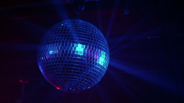 medium angle. looking up at spinning disco ball in nightclub. - ball video stock e b–roll