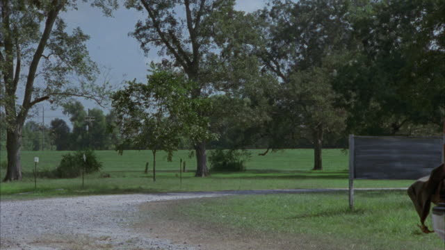medium angled view of dirt road or pathway with grass and trees surrounding. silver lincoln town car drivers down the path and stops. - lincoln town car stock videos and b-roll footage