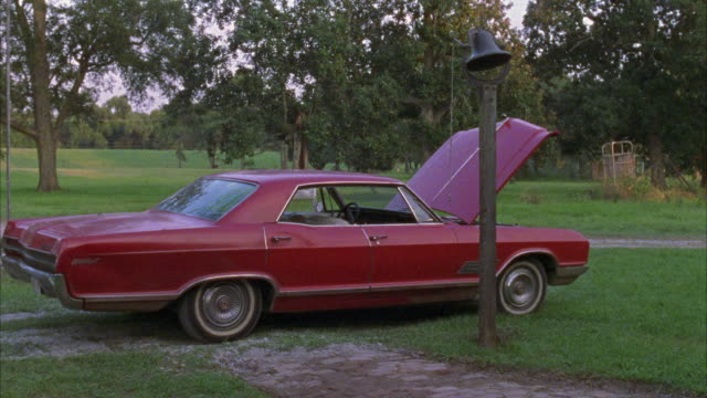 est medium angle red classic car, 1966 buick wildcat with hood propped up. grass with trees in bg, bell, possibly from schoolhouse in fg. - collector's car stock videos & royalty-free footage