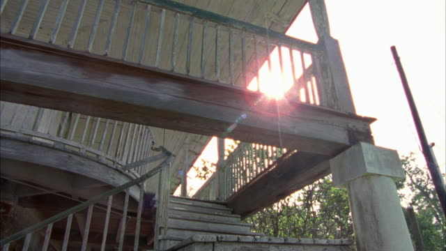up angle view of wooden staircase and porch, balcony with peeling paint with sunlight beaming through. camera pans down to bottom of staircase. abandoned, rundown house could be old plantation, colonial style. two story. - zweistöckiges wohnhaus stock-videos und b-roll-filmmaterial