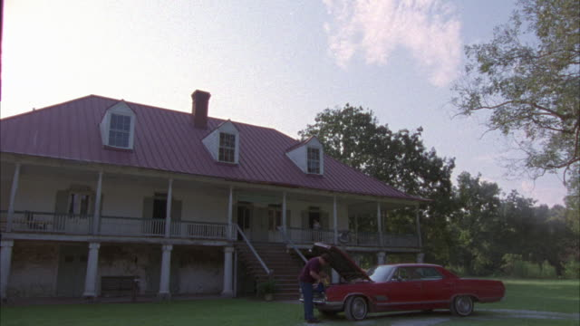 wide angle. est two story house with red shingled roof and one chimney. steps lead to second floor. red car parked out front with man inspecting under the hood. trees, sky and clouds in bg. - zweistöckiges wohnhaus stock-videos und b-roll-filmmaterial