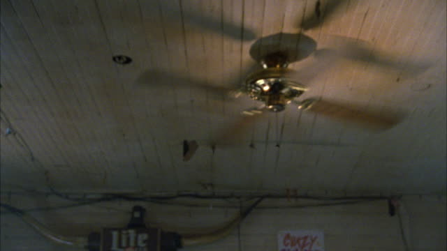 "up angle. white ceiling fan with four blades spinning on white, slightly-dirty ceiling. sign for light beer  ""lite"" on bottom of shot. could be general store, bar, market. - ceiling fan stock videos & royalty-free footage"