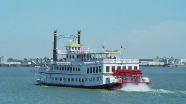 wide angle of riverboat or ferry on river. camera zooms out and zooms back to riverboat. could be tour boat. see piers in background. paddlewheelers. mississippi river. - paddle boat stock videos & royalty-free footage