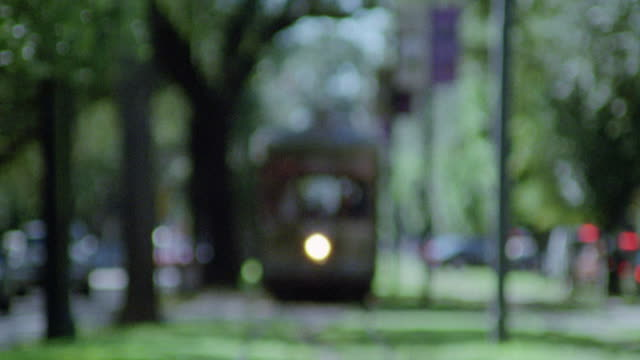 """est medium angle, front view of st. charles avenue streetcar, which runs on shade-covered grass meridian between two one way streets. streetcar stops to let passengers off, then continues route. see """"st charles"""" sign on top front of vehicle. - one way stock videos & royalty-free footage"""