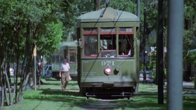 """est medium angle, front view of st. charles avenue streetcar, which runs on shade-covered grass meridian between two one way streets.  see """"st charles"""" sign on top front of vehicle. - one way stock videos & royalty-free footage"""