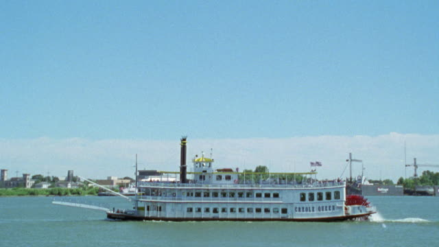 """wide angle of ferry or riverboat. camera zooms into paddle wheel, """"creole queen"""" is painted on boat. see people on decks, could be tour boat. mississippi river. paddlewheelers. tourists. - nautical vessel stock videos & royalty-free footage"""