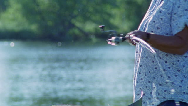 close angle on woman adjusting fishing pole.  woman throws fishing line into river and reels in fishing line. could be mississippi river. - mississippi river stock videos & royalty-free footage