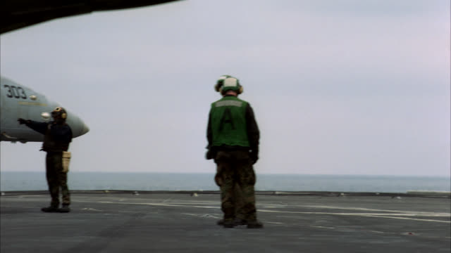 wide angle of military personnel standing under the afterburner of a fighter jet or military airplane on an aircraft carrier. - afterburner stock videos and b-roll footage