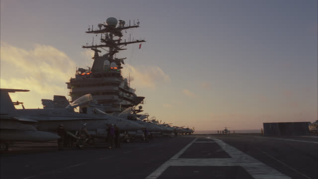 pan left to right and back across several fa-18 hornet fighter jets.  the military airplanes lined up in front of the control tower or radar tower. military personnel inspect the planes. aircraft carrier. - back to front stock videos & royalty-free footage