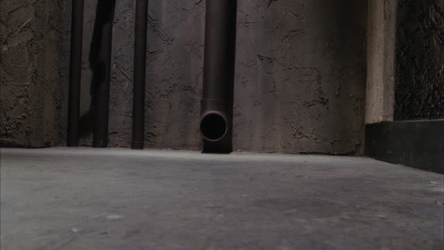 vídeos de stock, filmes e b-roll de close angle of metal ball rolling out of pipe across cement floor. could be basement or cell. could be bomb. - bola