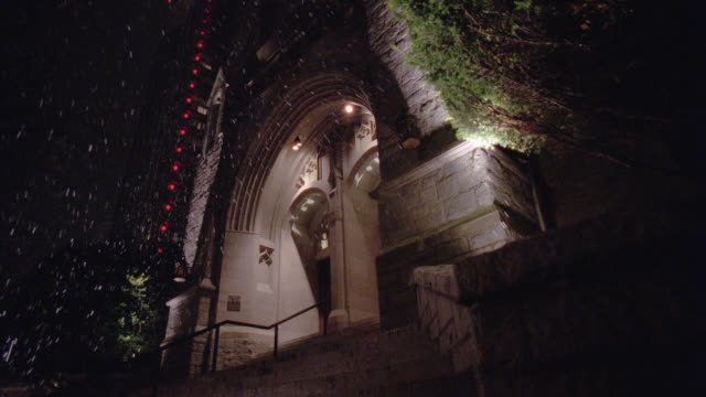 up angle of entrance of church or cathedral in city. high rises building with red lights next to church. ivy and arched entrance. rain falls from sky. - falls church stock videos & royalty-free footage