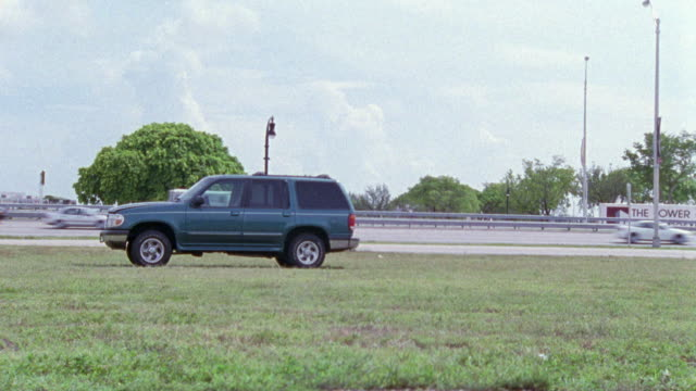 wide angle shot of hunter green ford explorer parked in the grass next to freeway. suvs. - sports utility vehicle stock videos and b-roll footage