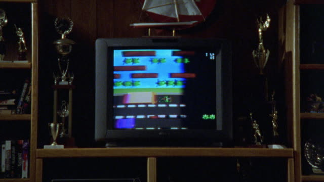 medium angle. insert of television. the video game 'frogger' comes onto the screen. 'game over' comes on screen and then high score list comes on. - di archivio video stock e b–roll
