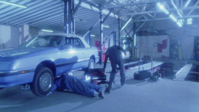 medium angle. inside auto repair shop. blue chrysler le baron on lifts. repair man, mechanic underneath doing work. only neck down visible. two more workers walk by. camera moves slightly from r-l. garage is hazy. shot at 30 fps. cars. - mechanic stock videos & royalty-free footage