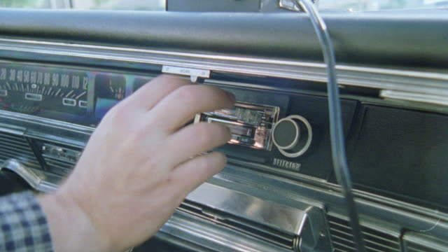 CLOSE ANGLE. INSERT OF HAND TAKING CASSETTE OUT OF STEREO IN CAR DASHBOARD. VINTAGE INTERIOR.