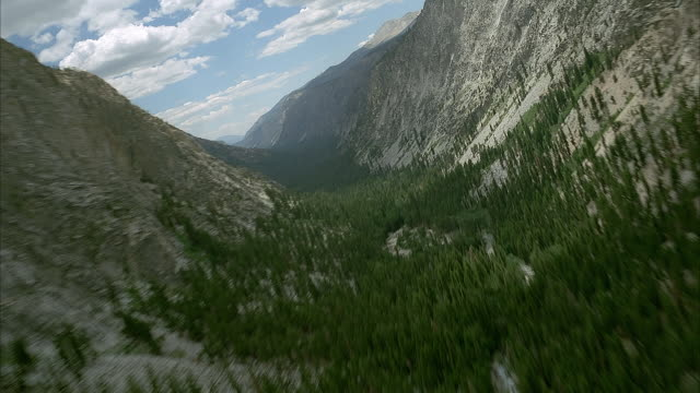 aerial flying pov over gray rocky snow speckled mountains. see coniferous forest sprinkled throughout. see denser forest at bottom along curving river. pov flies through valley. see cumulus clouds in blue sky. - valley stock videos & royalty-free footage