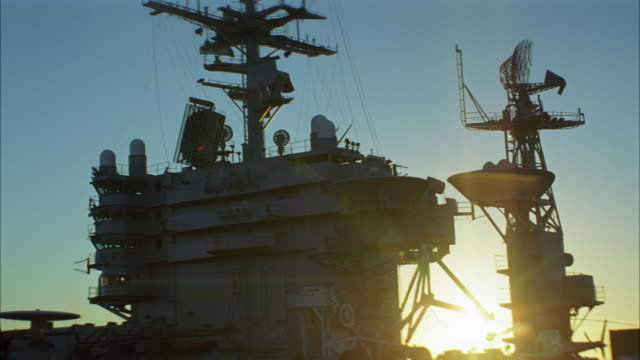 wide angle  of deck of navy aircraft carriers. ec-2 hawkeye parked and secured to deck. radar antennas scan horizon. sunset behind control tower. - aircraft carrier stock videos & royalty-free footage