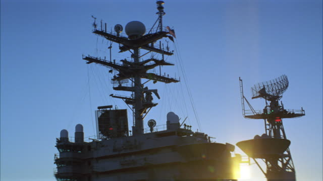 pan down of control tower and radar tower of navy aircraft carrier. radar antenna scans horizon. e2-c hawkeye and bell h-1 huey parked and secured to deck. sun halations. sunset behind control tower. - military ship stock videos & royalty-free footage
